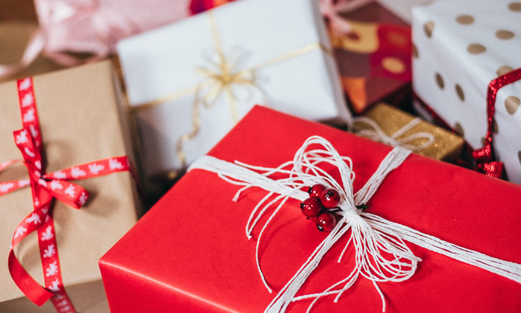 Closeup of a cluster of holiday gifts wrapped in red, brown, and white paper for Christmas