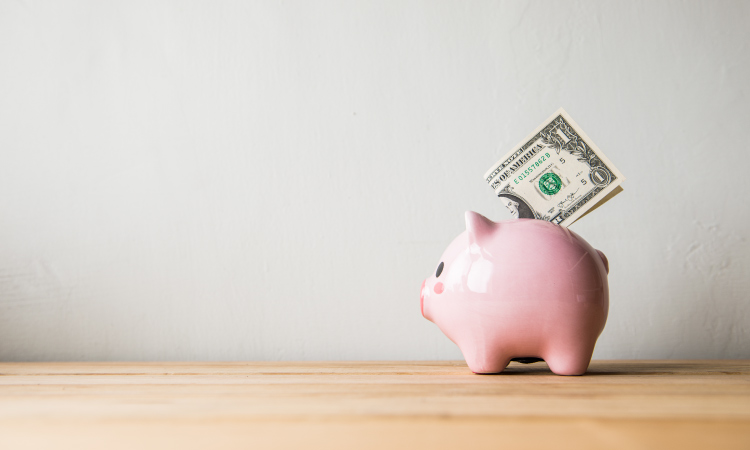 A pink piggy bank holds a one dollar bill on a brown counter against a white wall