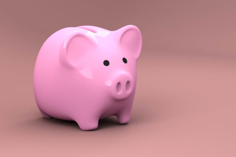 A pink piggy bank against a pink background used for saving money from affordable dental care at Heritage Dental