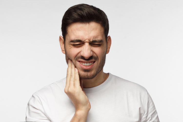 Brunette man in a white shirt cringes and touches his cheek due to pain from a toothache