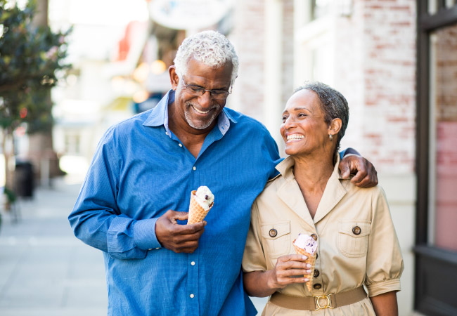 Husband and wife smile and walk down the sidewalk with ice cream cones discussing dental implants vs. dentures