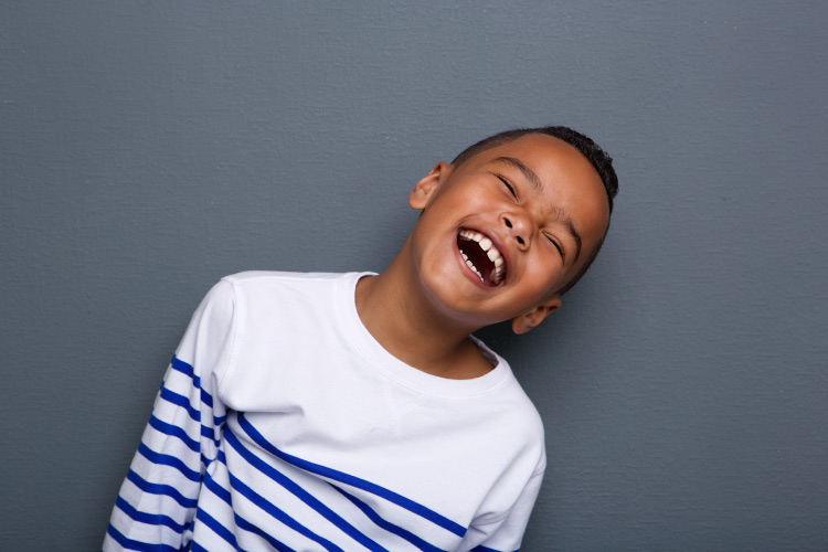 Young boy in a blue and white striped shirt laughs after conquering his dental anxiety at Heritage Dental in Katy, TX
