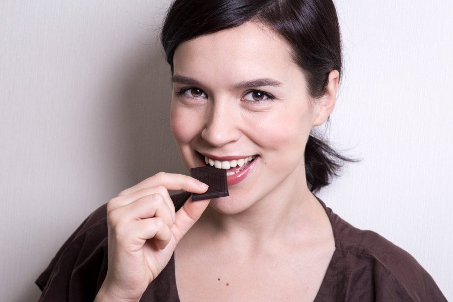 Brunette woman smiles as she eats a piece of dark chocolate in Katy, TX